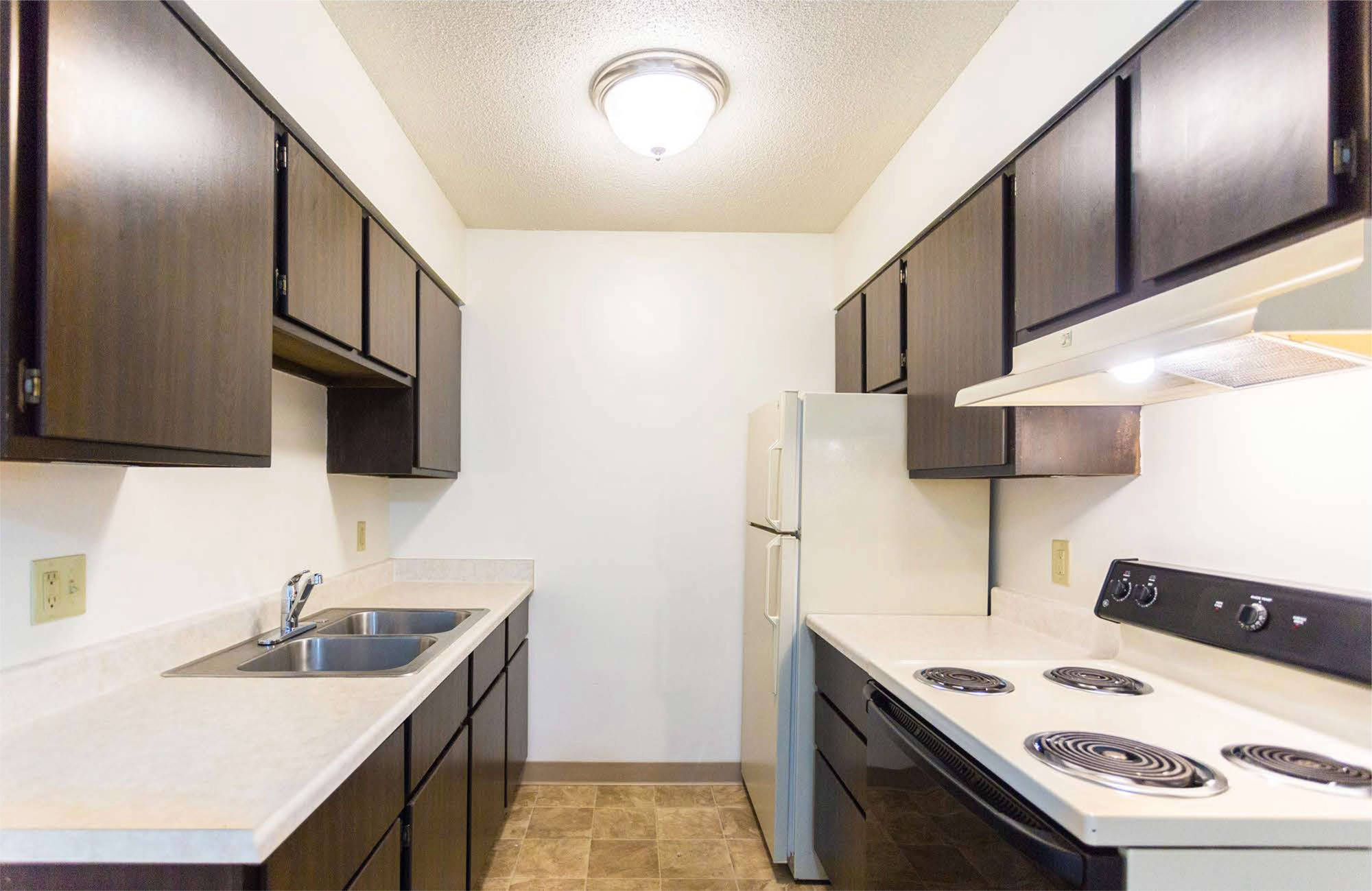 Kitchen with range, stove, refrigerator, sink and cabinets on both sides - Fairview Apartments in St. Peter, MN