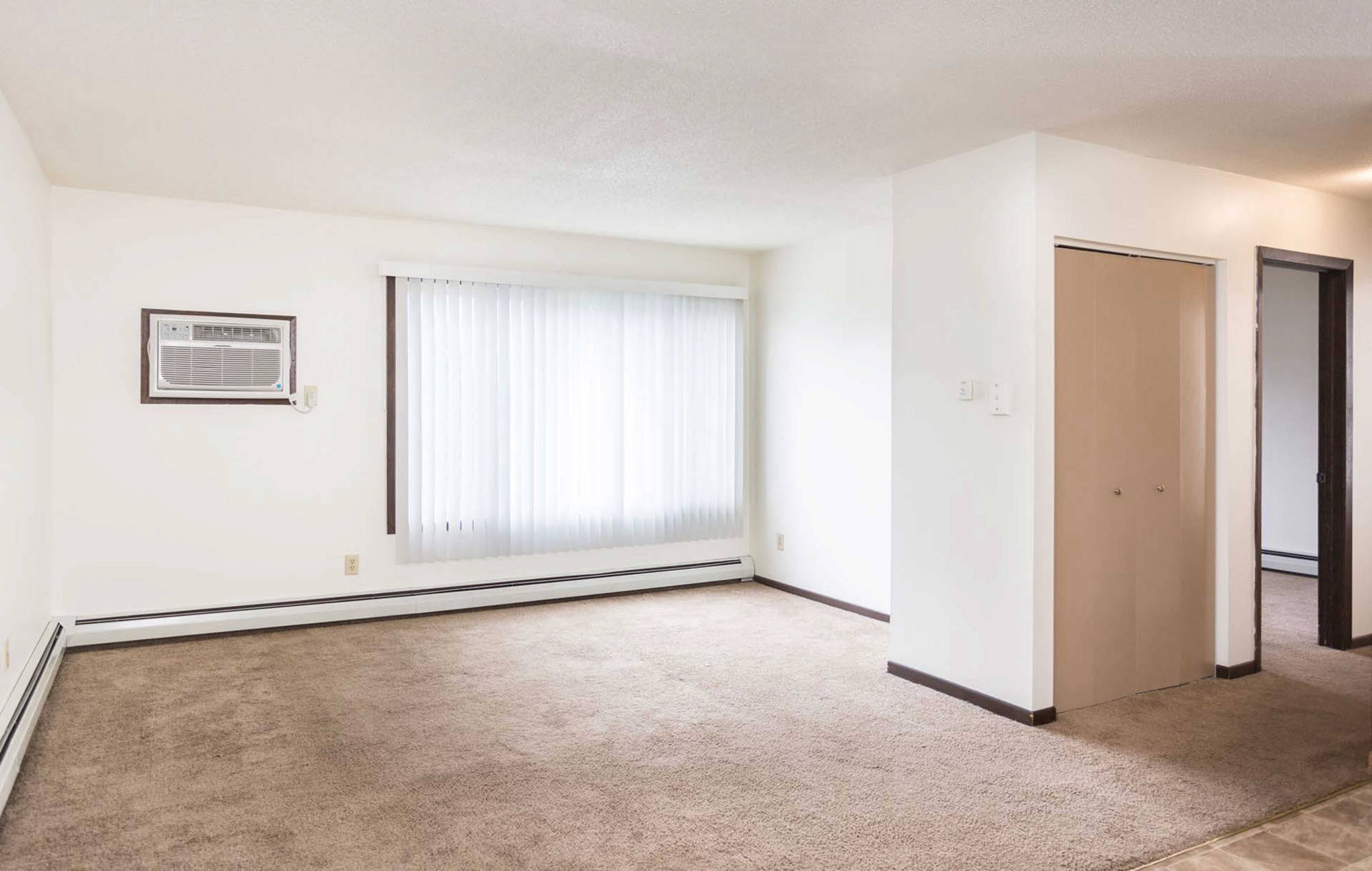 Living room with air conditioner, window with stylish shades, closet and carpeting. Fairview Apartments St. Peter, MN